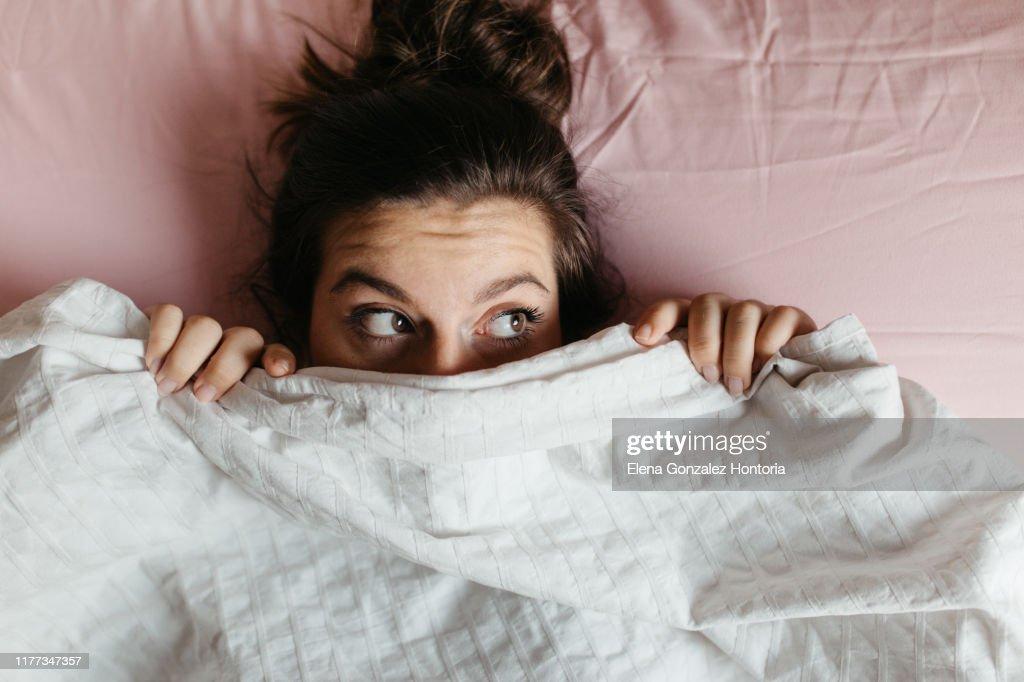 Erschrockene und überraschte junge Frau mit offenen Augen versteckt Gesicht unter Decke, ziemlich erschrocken und neugierig Mädchen gefühl schüchtern gucken aus Bettdecke, Abdeckung mit weißen Blatt, Kopf aus nächster Nähe geschossen. Ansicht von ob : Stock-Foto