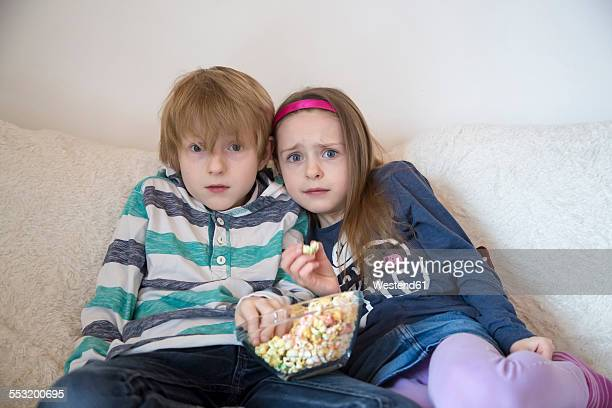 Scared brother and sister with bowl of coloured popcorn watching TV