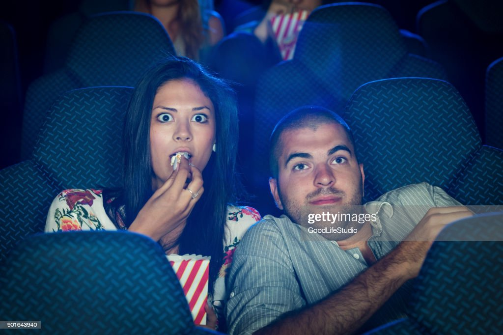 Scared couple in a cinema : Stock Photo