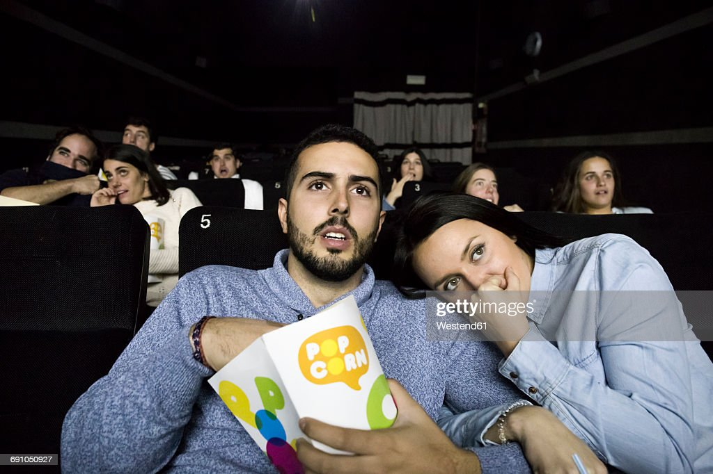 Scared couple watching a movie in a cinema : Stock Photo