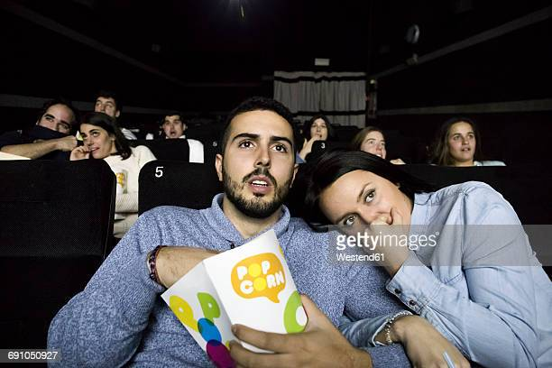 Scared couple watching a movie in a cinema