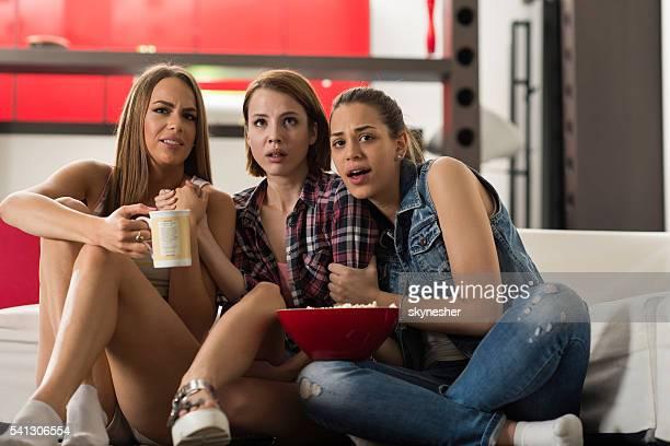 Paura femmina amici guardando un film insieme un casa.