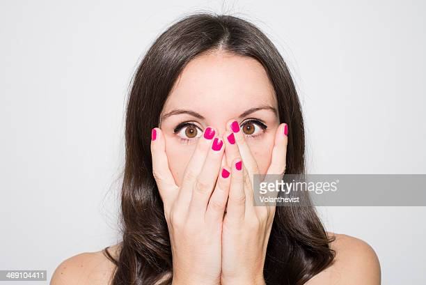 Scared girl with pink nails and hand on face.