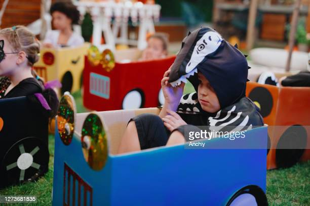 scared little boy hiding under his hoodie during movie night - scaredastronaut stock pictures, royalty-free photos & images