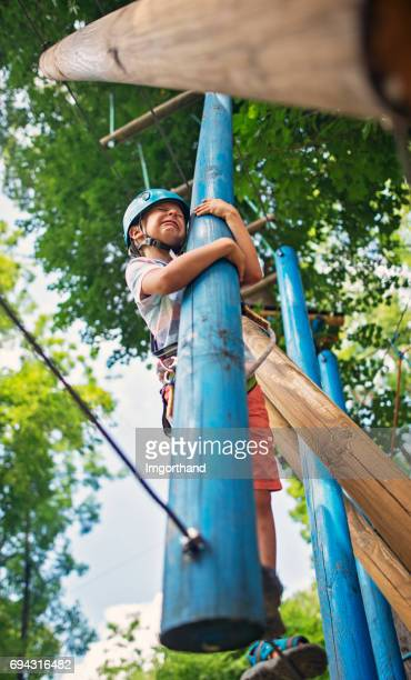 Scared little boy in ropes course