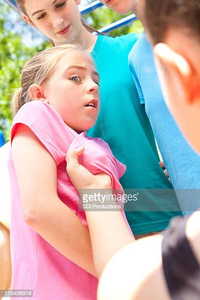 Scared little girl being bullied on the school playground