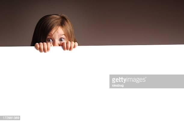 Peur de petite fille derrière un panneau blanc Regarder à la dérobée