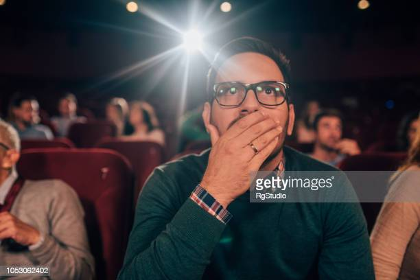 scared man at cinema - film screening stock pictures, royalty-free photos & images