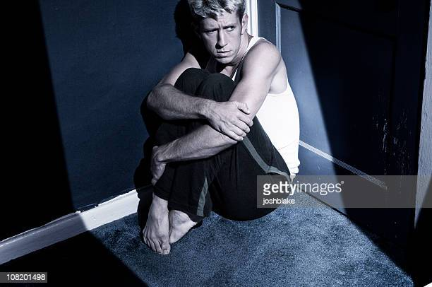 scared man hiding in dark corner - fetal position stock photos and pictures