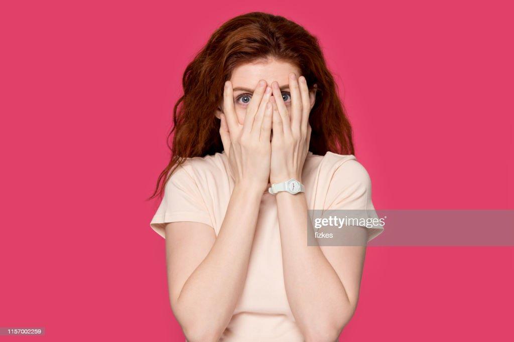 Scared redhead girl cover face peeking through fingers : Stock Photo