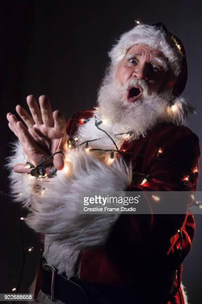 scared santa claus tied up / tangled in christmas lights - pere noel libre de droit photos et images de collection