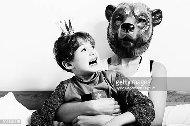 scared son looking at mother wearing mask at home - mama bear stock photos and pictures