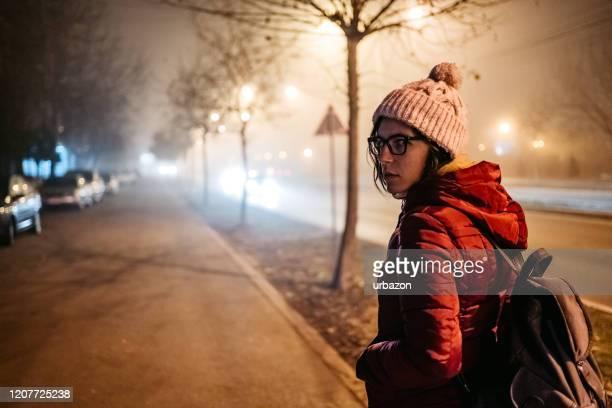 bange vrouw op straat in mistige nacht - angst stockfoto's en -beelden