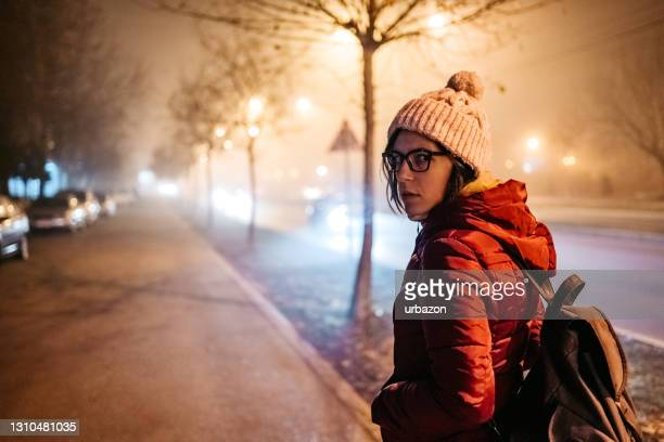 scared woman on street in foggy night - looking over shoulder stock pictures, royalty-free photos & images