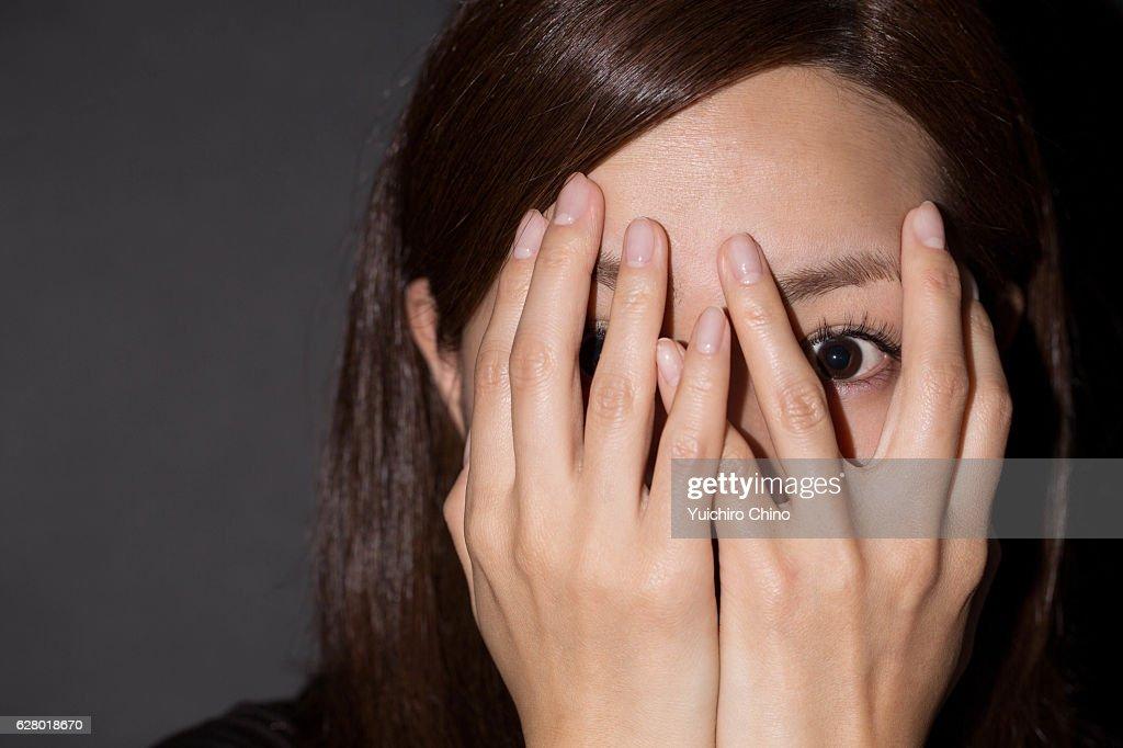 Scared woman peeking through her hands : Stock Photo