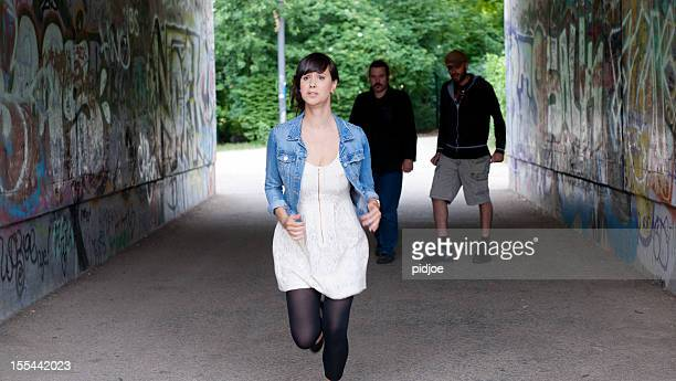 scared woman running in spooky tunnel - harassment stock photos and pictures