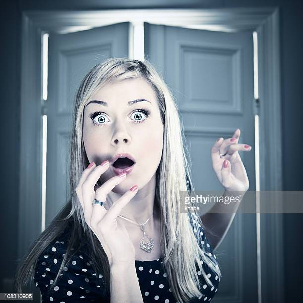 Scared woman with opening door behind her
