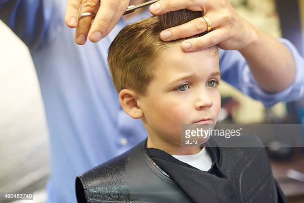 Scared young boy having his haircut