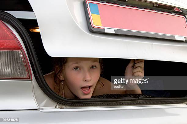 scared young girl in the trunk compartment.