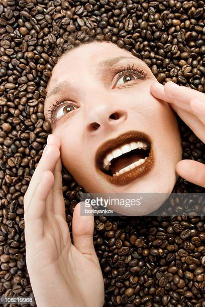 scared young woman buried in coffee beans - caffeine stock pictures, royalty-free photos & images