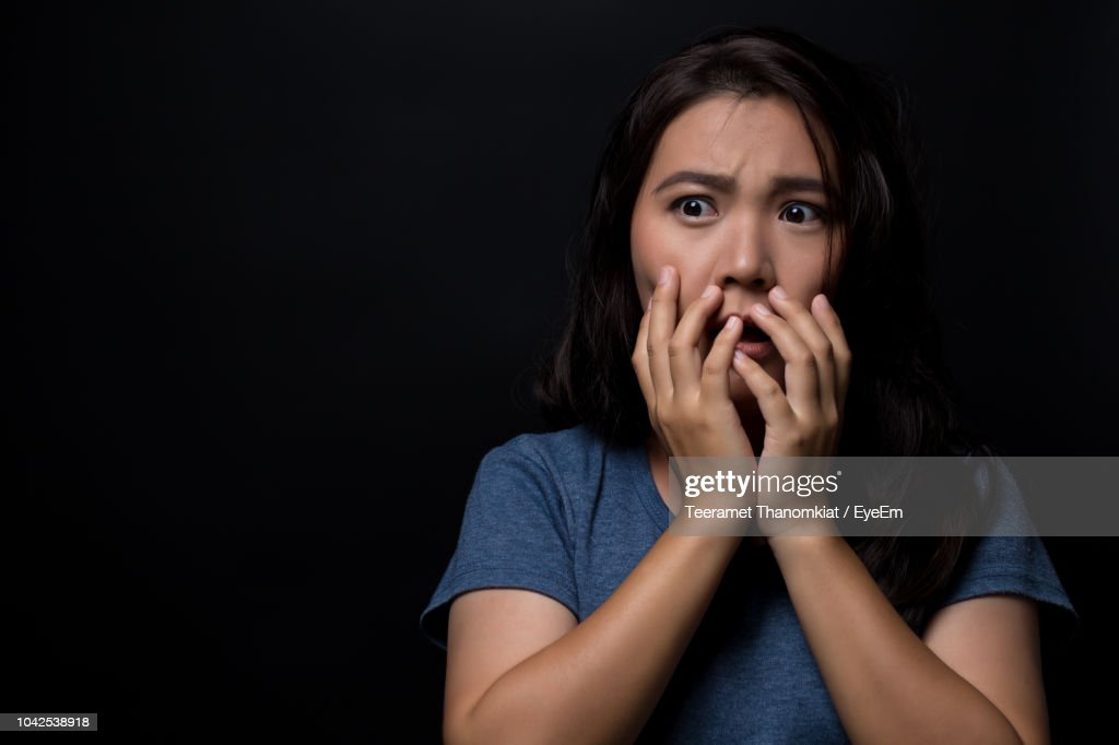Scared Young Woman Looking Away While Standing Against Black Background : Stock Photo