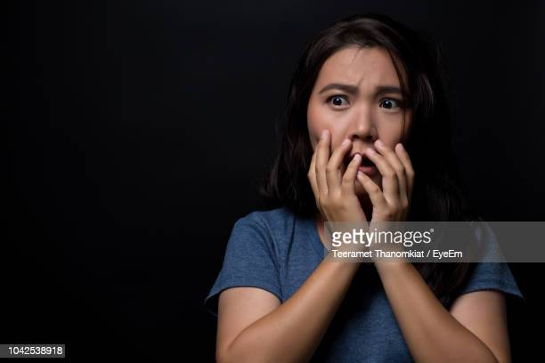 scared young woman looking away while standing against black background - fear stock pictures, royalty-free photos & images