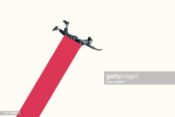 scared young woman lying on falling red bar graph - graphic accident photos stock pictures, royalty-free photos & images