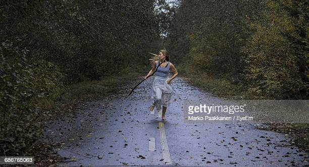 scared young woman running on footpath in forest - female torture stock-fotos und bilder