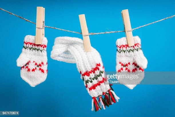 scarf and pair of gloves drying on the rope