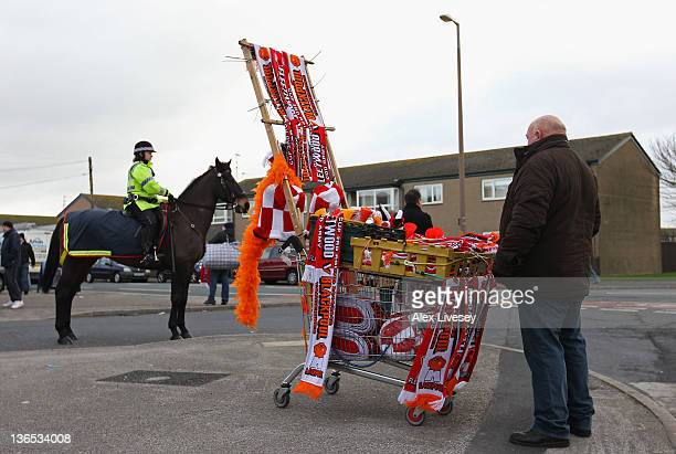 A scarf seller is seen outside the Highbury Stadium prior to the FA Cup sponsored by Budweiser third round match between Fleetwood Town and Blackpool...