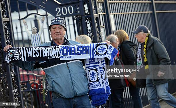 A scarf seller stands at the Jeff Astle Gates of West Bromwich Albion