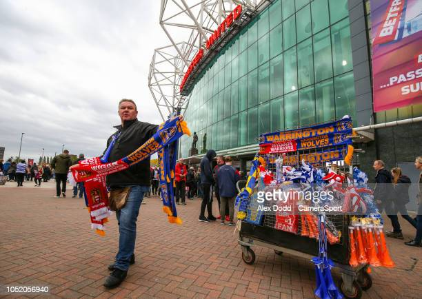 A scarf seller works outside Old Trafford before the Super League Grand Final between Wigan Warriors and Warrington Wolves during the Betfred Super...