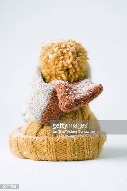 Scarf wrapped around knit hat, snow-covered