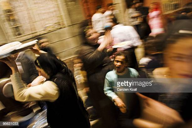 Scarfed woman shares out sweets to the dancing guests at a wedding party in the district Tarlabasi on May 14, 2006 in Istanbul, Turkey. Tarlabasõ is...