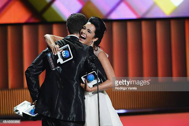 Scarlet Gruber receives an award presented by Christian De La Campa onstage at Telemundo's Premios Tu Mundo Awards 2015 at American Airlines Arena on...