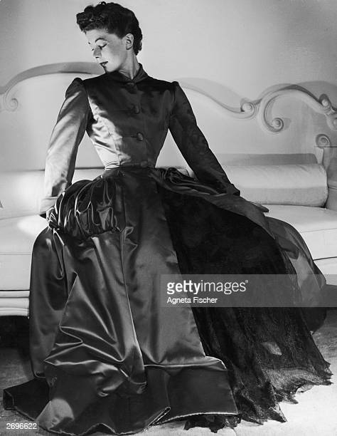Scarlet satin coat with panniers worn over a hooped gown of black lace, by Balenciaga. An example of the lavish fashions which were to be produced by...