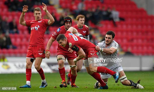 Scarlets centre Scott Williams breaks the tackle of Charles Ollivon during the European Rugby Champions Cup match between Scarlets and RC Toulonnais...