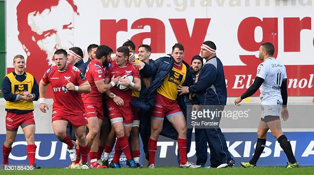 Scarlets centre Scott Williams celebrates his opening try with team mates during the European Rugby Champions Cup match between Scarlets and RC...