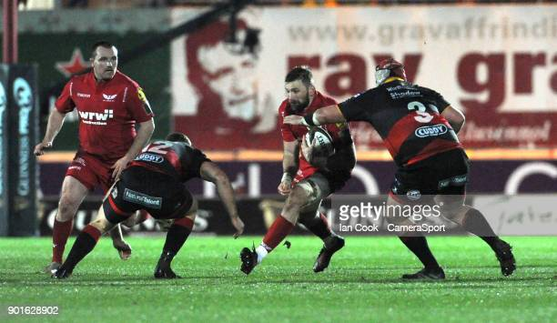 Scarlets' John Barclay takes on Dragons Jack Dixon and Nicky Thomas during the Guinness Pro14 Round 13 match between Scarlets and Dragons at Parc y...