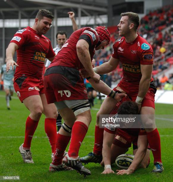 Scarlets players celebrate after Nic Reynolds scored a try during the LV= Cup match between Scarlets and Leicester Tigers at Parc y Scarlets on...