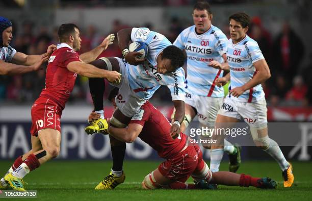 Scarlets players Gareth Davies and Ed Kennedy combine to tackle Racing player Leone Nakarawa during the Champions Cup match between Scarlets and...
