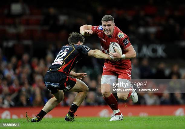 Scarlets' Scott Williams is tackled by Dragons' Sam Beard during the Guinness PRO12 Round 20 match between Newport Gwent Dragons and Scarlets at...
