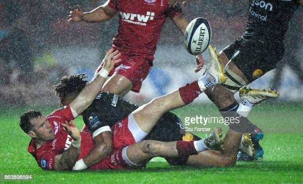 Scarlets scrum half Gareth Davies off loads to set up the first try despite the efforts of Anthony Watson during the European Rugby Champions Cup...
