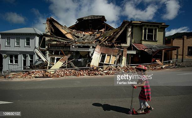Scarlett Corbett rides past the damaged theatre in the center of Lyttleton after the 6.3 magnitude earthquake, on February 24, 2011 in Christchurch,...