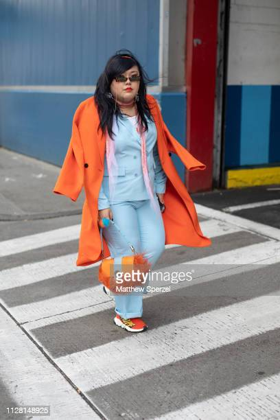 Scarlett Hao is seen on the street during New York Fashion Week AW19 wearing baby blue suit with orange wool coat and orange fur bag on February 07...