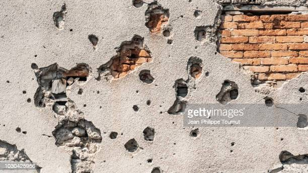 scars from a painful past - bullet holes in a wall in mostar, bosnia and herzegovina - konflikt stock-fotos und bilder