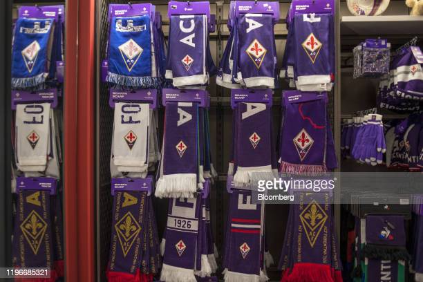 Scarves featuring ACF Fiorentina badges hang for sale with other merchandise in Florence Italy on Sunday Jan 12 2020 Rocco Commisso who grew up in...