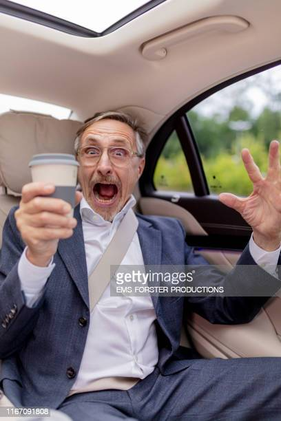 scary businessman is sitting in his limousine while holding his coffee cup - caricature stock pictures, royalty-free photos & images