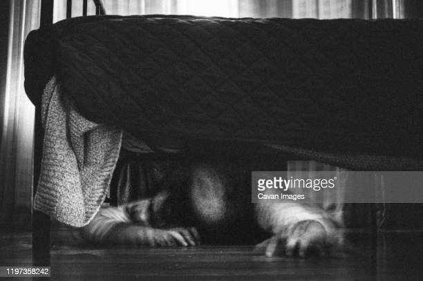 scary ghost girl crawling out from underneath the bed - goose bumps stock pictures, royalty-free photos & images