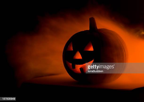 a scary halloween pumpkin in smoke  - jack o' lantern stock photos and pictures